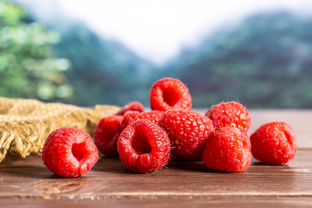 Lot of whole fresh red raspberry on jute cloth in a foggy jungle mountains Фото со стока