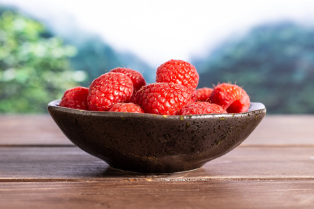 Lot of whole fresh red raspberry on grey ceramic plate in a foggy jungle mountains