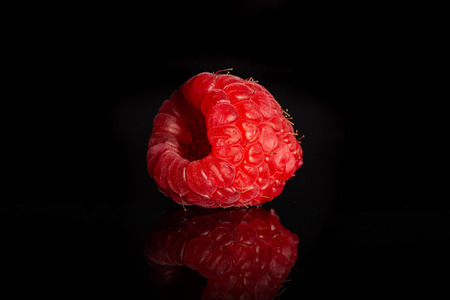 One whole fresh red raspberry isolated on black glass