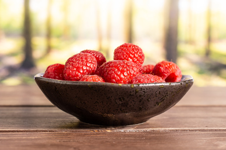 Lot of whole fresh red raspberry on grey ceramic plate in a forest