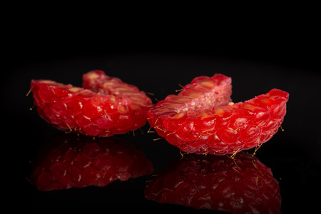 Group of two halves of fresh red raspberry isolated on black glass