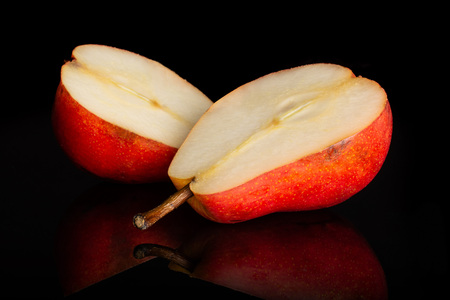 Group of two halves of fresh red pear isolated on black glass Фото со стока