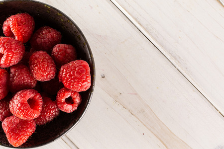 Lot of whole fresh red raspberry on grey ceramic plate flatlay on white wood
