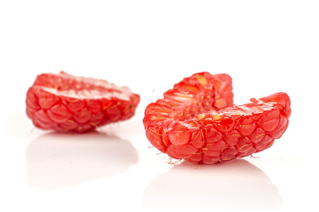 Group of two halves of fresh red raspberry isolated on white Фото со стока