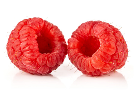 Closeup of two whole fresh red raspberry isolated on white