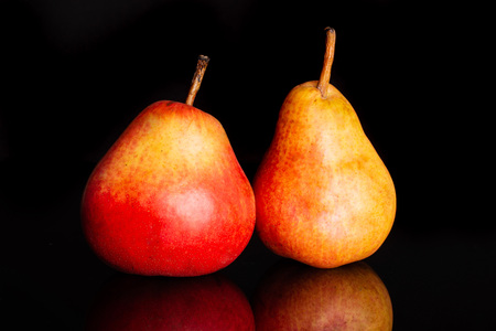 Group of two whole fresh red pear isolated on black glass Фото со стока