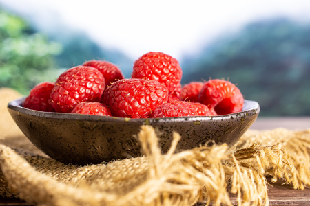Lot of whole fresh red raspberry on grey ceramic plate on jute cloth in a foggy jungle mountains Фото со стока