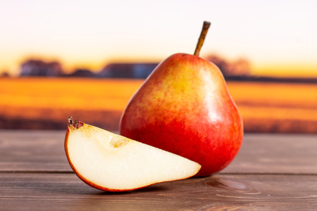 Group of one whole one slice of fresh red pear with autumn field