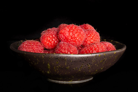 Lot of whole fresh red raspberry on grey ceramic plate isolated on black glass