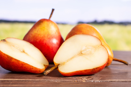 Group of two whole two halves of fresh red pear with green wheat field