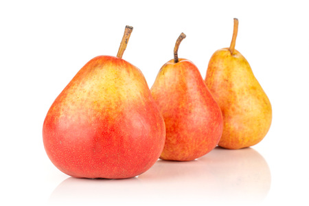 Group of three whole fresh red pear in row isolated on white