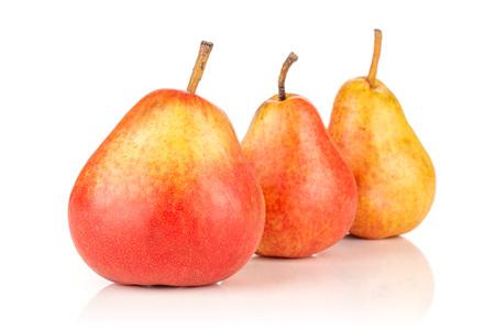 Gruppe von drei ganzen frischen roten Birnen in Reihe isoliert auf weiß
