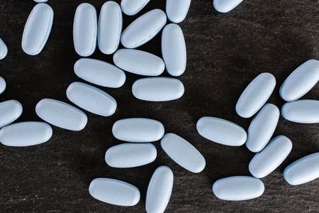 Lot of whole light blue medical drug flatlay on grey stone