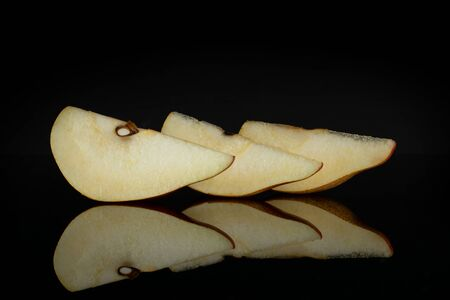 Group of three slices of fresh dark red pear anjou in row isolated on black glass Stock fotó
