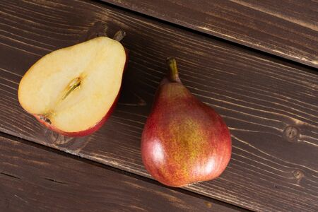 Group of one whole one half of fresh dark red pear anjou flatlay on brown wood