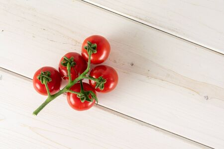 Group of five whole fresh red tomato cherry flatlay on white wood