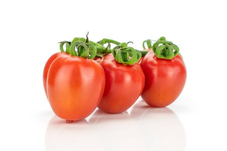 Group of three whole fresh red tomato cherry isolated on white background