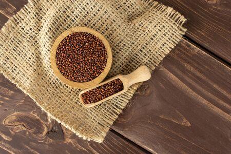 Beaucoup de graines entières de quinoa rouge cru dans un bol en bois sur toile de jute avec cuillère en bois flatlay sur bois marron