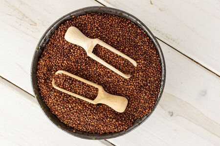 Lot of whole raw red quinoa seeds in a grey ceramic bowl with wooden scoop flatlay on white wood