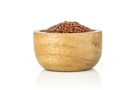 Lot of whole hulled raw red quinoa seeds in a wooden bowl isolated on white background