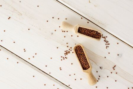 Lot of whole raw red quinoa seeds copyspace with wooden scoop flatlay on white wood