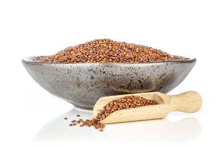 Lot of whole hulled raw red quinoa seeds in a grey ceramic bowl with wooden scoop isolated on white background Zdjęcie Seryjne