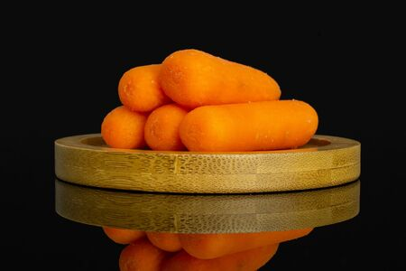 Group of five whole peeled orange baby cut carrot on bamboo plate isolated on black glass