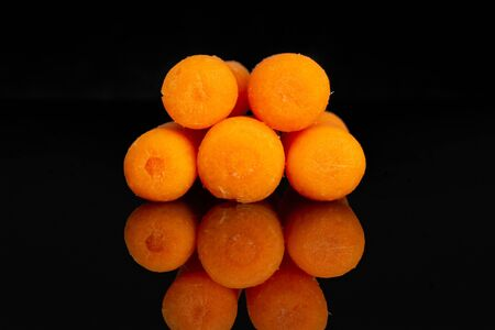 Group of five whole peeled orange baby cut carrot isolated on black glass Reklamní fotografie