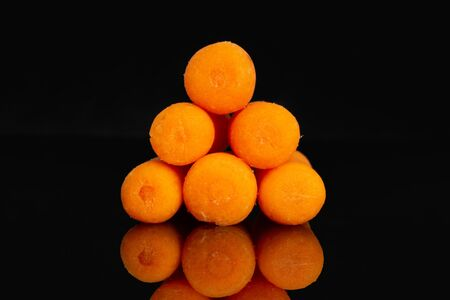 Group of six whole peeled orange baby cut carrot pyramid isolated on black glass