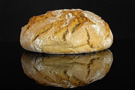One whole fresh baked rye wheat bread loaf isolated on black glass Archivio Fotografico