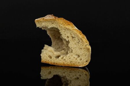 One pinched off fresh baked rye wheat bread slice isolated on black glass