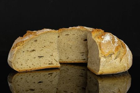 Group of one half two slices of fresh baked rye wheat bread isolated on black glass