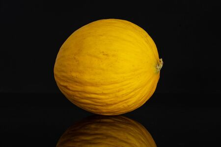 One whole fresh yellow melon canary isolated on black glass
