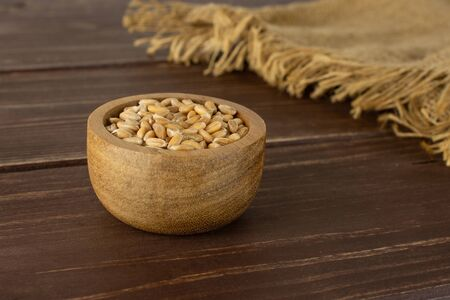 Lot of whole fresh beige dinkel wheat grain in a wooden bowl and jute cloth on brown wood Banque d'images