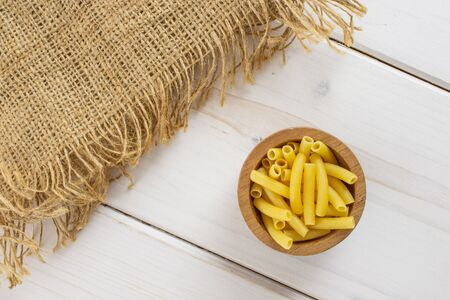 Lot of whole raw pasta macaroni in a wooden bowl with jute cloth flatlay on white wood Banque d'images