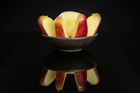 Group of one half four slices of fresh apple red delicious in a dark ceramic bowl isolated on black glass 写真素材