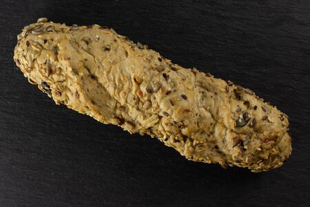 One whole fresh cereal baguette flatlay on grey dark stone