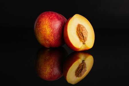 Group of one whole one half of fresh red nectarine isolated on black glass Фото со стока
