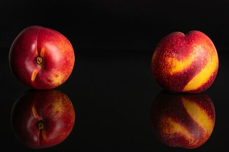 Group of two whole fresh red nectarine isolated on black glass