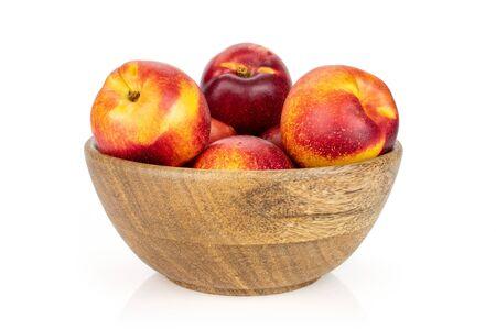 Beaucoup de nectarine rouge fraîche entière dans un grand bol en bois isolé sur fond blanc