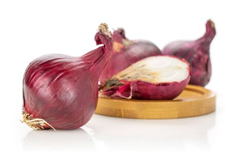 Group of three whole one half of stale red onion on bamboo plate isolated on white background Reklamní fotografie
