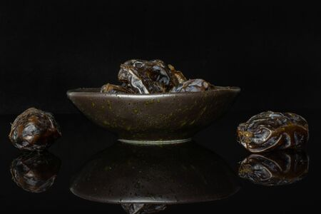 Lot of whole dried brown date medjool on grey ceramic plate isolated on black glass