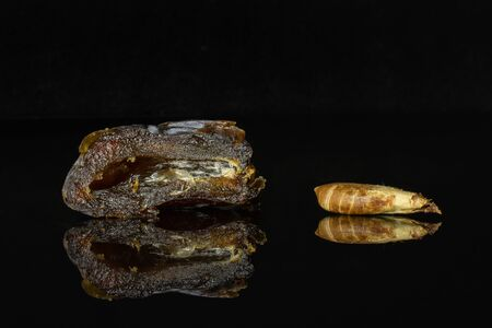 Group of one half one piece of dried brown date medjool isolated on black glass Stock Photo