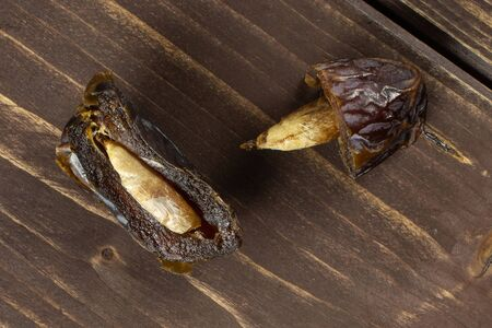 Group of two halves of dried brown date medjool flatlay on brown wood Stock Photo