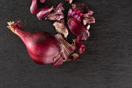 One whole lot of pieces of stale red onion flatlay on grey stone