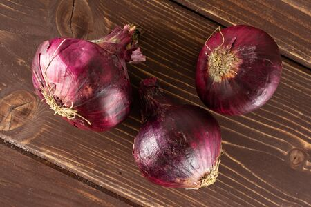 Group of three whole stale red onion flatlay on brown wood