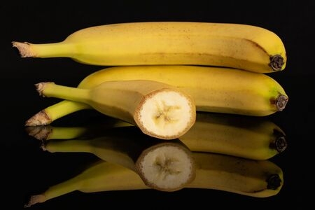 Group of two whole one half of ripe yellow banana isolated on black glass