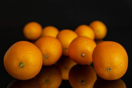 Lot of whole fresh orange kumquat arranged symmetrically isolated on black glass