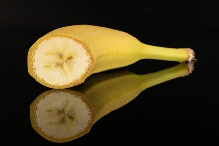 One half of ripe yellow banana isolated on black glass
