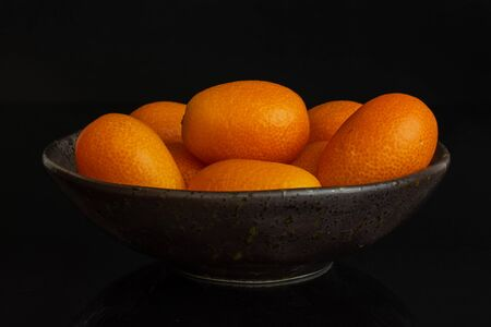 Lot of whole fresh orange kumquat in a dark ceramic bowl isolated on black glass